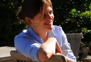 Kate Heschl, auf einem Sessel in der Natur sitzend
