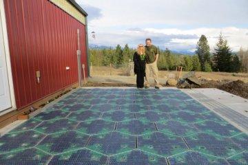 Die Unternehmensgründer stehen auf einer Reihe von Solarplatten