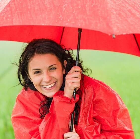 nicht nur durch positives Denken: positiv gestimmte, fröhliche Frau mit Regenschirm