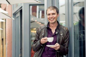 Foto von Kimbal Musk vor The Kitchen mit einer Tasse Kaffee in der Hand