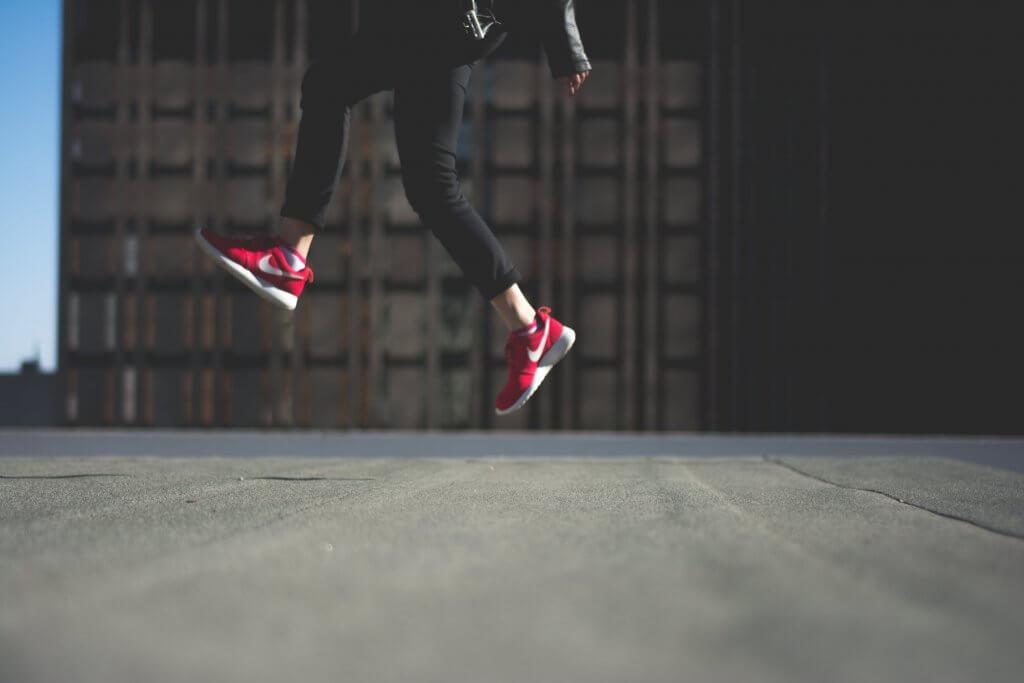 Luftsprung mit roten Schuhen