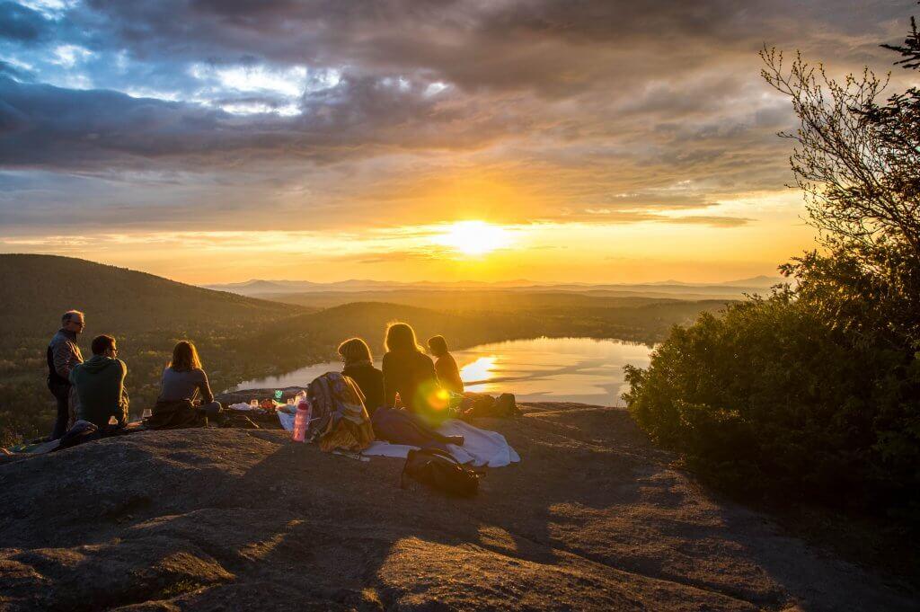 eine Gruppe von Freunden macht ein Picknick im Sonnenuntergang