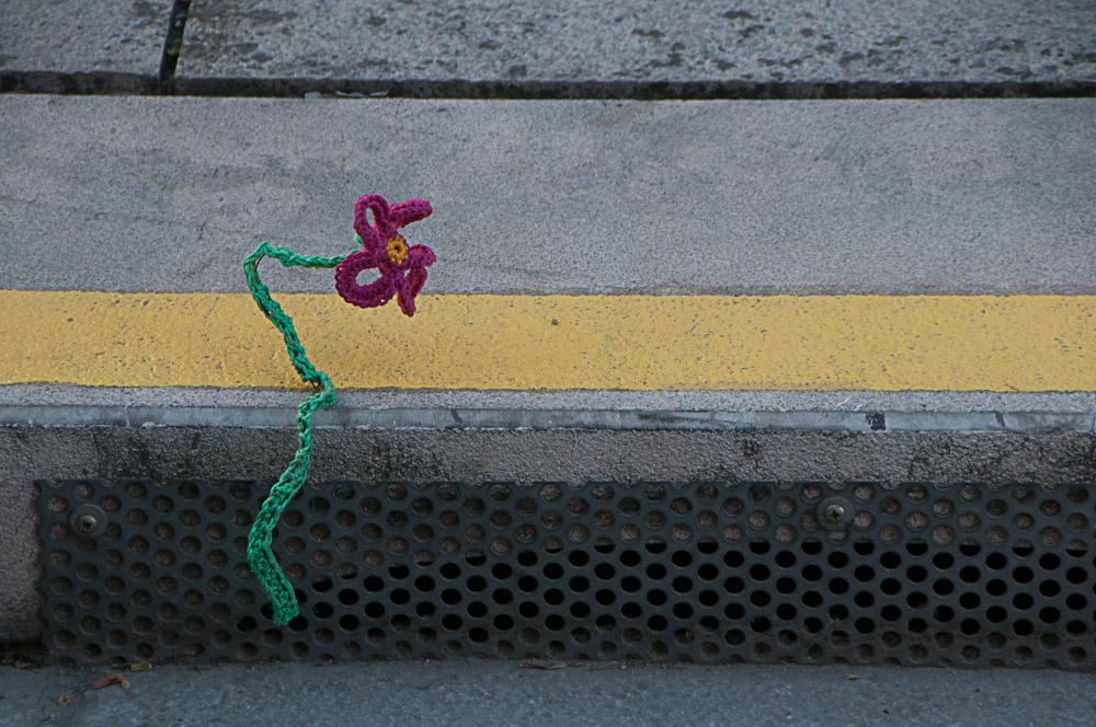Eine Häkelblume am Straßenrand als Symbol für die Zero Waste Challenge