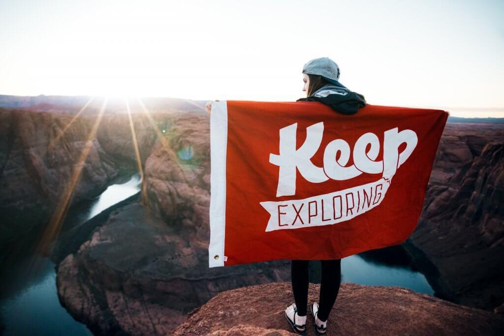 Flagge zeigen: Mädchen mit Keep Exploring Fahne auf einem Felsvorsprung
