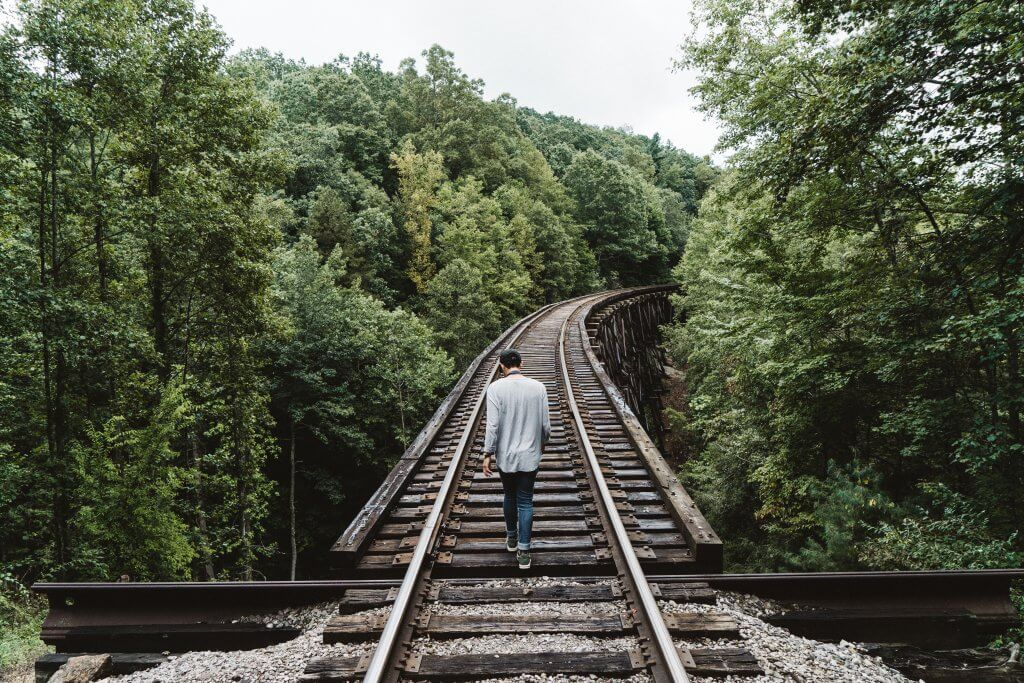 junger Mann geht auf Zuggleisen