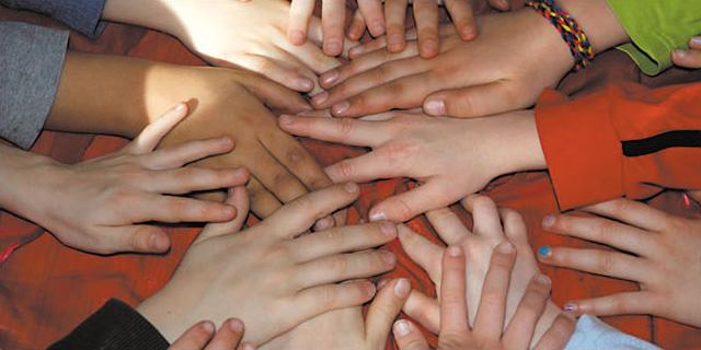 viele Kinderhände, auf einen Haufen gelegt