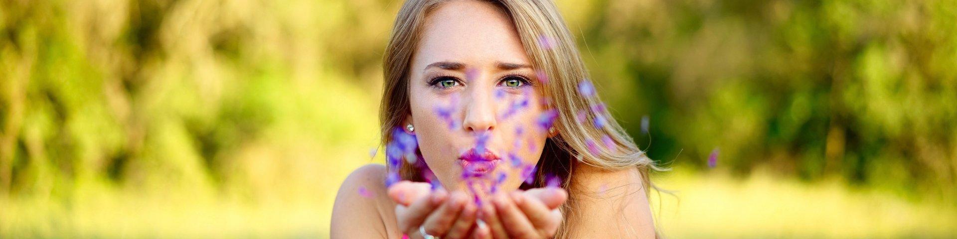 eine Frau hält Blüten in der Hand und bläst sie weg