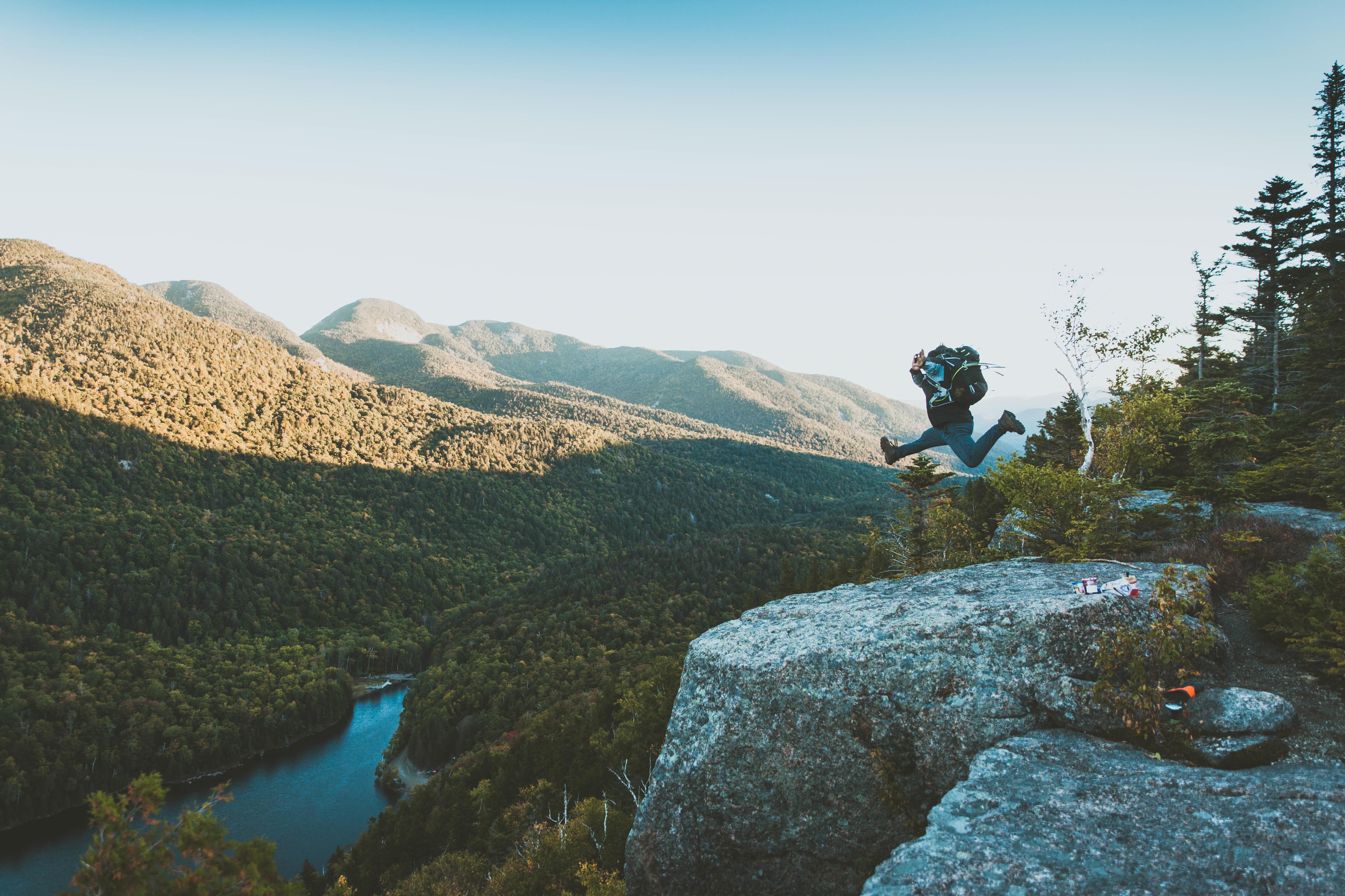 Luftsprung auf einem Felsen als Symbol für mutmachende Sprüche