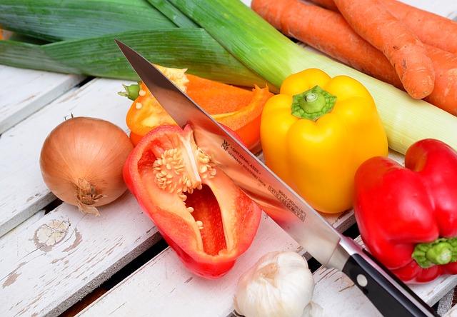 Gemüse und Gemüseschnipsel auf einem Tisch mit Messer, das gerade schneidet