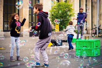 spielerisches Mitgestalten: Kinder machen Seifenblasen
