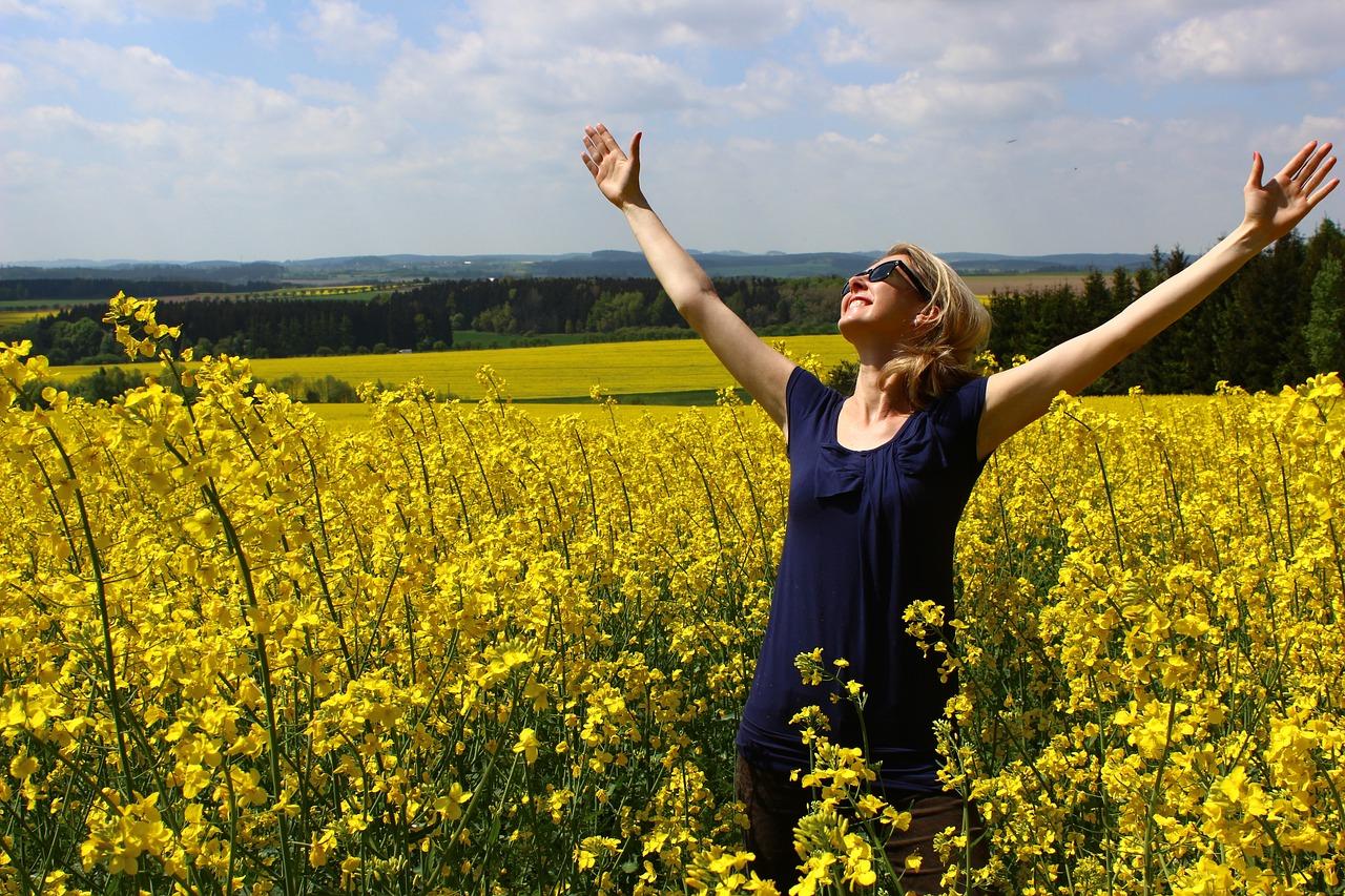 Frau mit dankbar erhobenen Armen in einer Blumenwiese