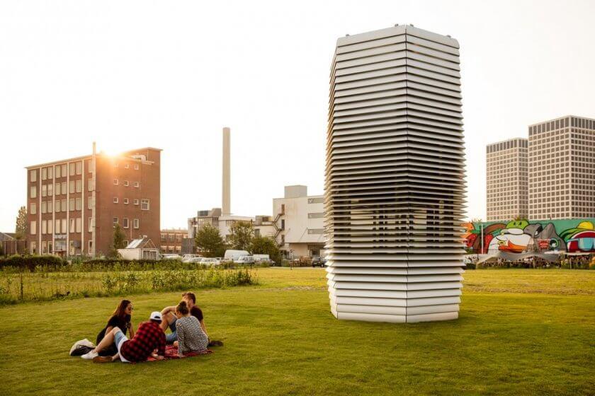 Der Smog Free Tower in einem Park, junge Leute sitzen daneben im Gras