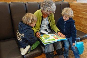 Frau liest zwei Kindern aus Buch vor