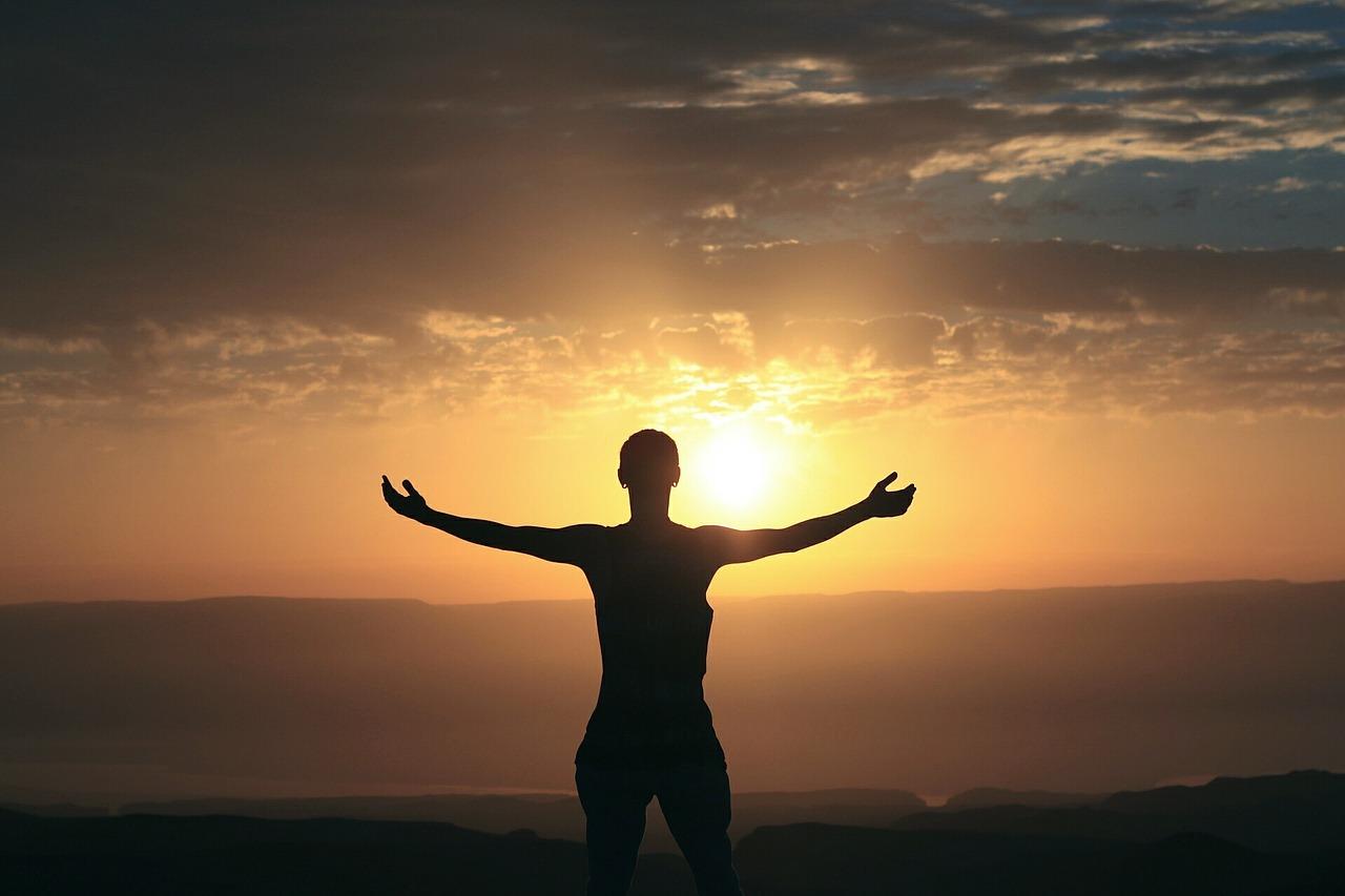 Mensch zeigt Dankbarkeit vor einem Sonnenuntergang